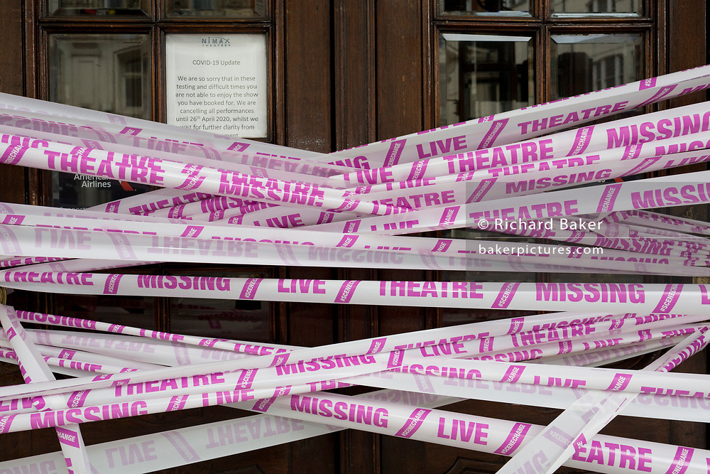 """The UK government has announced a Coronavirus pandemic financial rescue package for the Arts industry, a £1.15bn support for cultural organisations in England which is made up of £880m in grants and £270m of repayable loans. But venues such as The Apollo Theatre on Shaftesbury Avenue in London's West End Theatreland, where the musical Jamie was abandoned at the beginning of lockdown, will remain closed for the foreseeable future, on 6th July 2020, in London, England. Some theatres in London and others around the country have been wrapped in bright pink barrier tape, which reads """"Missing Live Theatre"""" -  a protest project led by stage designers group Scene Change highlighting the closure of the arts and culture arts industry supports 137,250 jobs and is worth £21.2bn in direct turnover."""