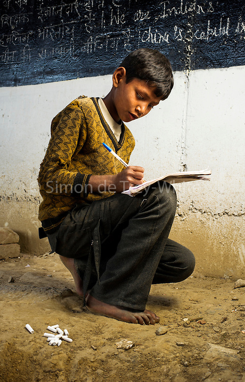 26th March 2014, Shakarpur, New Delhi, India. Govind Mauyra (12) copies from a blackboard at a makeshift school under a metro bridge near the Yamuna Bank Metro station in Shakarpur, New Delhi, India on the 26th March 2014<br /> <br /> Rajesh Kumar Sharma (born 01/02/1970), started this makeshift school in 2011. Six mornings a week he teaches underprivileged children for three hours while his younger brother replaces him at his general store in Shakarpur. His students are children of labourers, rickshaw-pullers and farm workers. This is the 3rd site he has used to teach under privileged children in the city, he began in 1997. <br /> <br /> PHOTOGRAPH BY AND COPYRIGHT OF SIMON DE TREY-WHITE<br /> + 91 98103 99809<br /> email: simon@simondetreywhite.com photographer in delhi