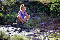 A woman sits by a mountain creek on Whistler Mountain, BC, Canada.