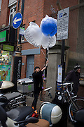 Woman carries oversized party balloons to a nearby venue in London's Soho.