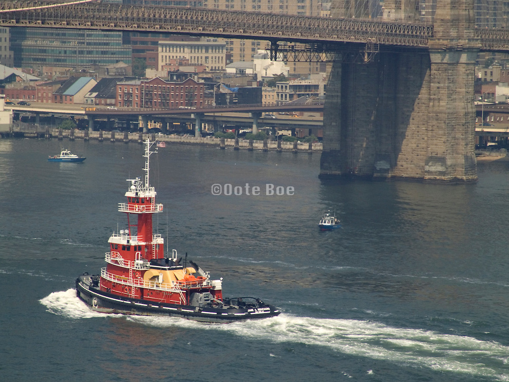 tugboat going under the Brooklyn bridge with two police boats nearby