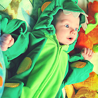 Young infant baby wears a dinosaur costume and looks surprised.