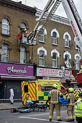 © Licensed to London News Pictures. 01/04/2020. London, UK. An aerial platform is used at an incident involving all emergency services a suspected COVID-19 case is isolated and removed from home. Uxbridge Road in Shepherd's Bush was closed for an hour as ambulance, fire brigade and police attended, extracting the patient by crane from a three story apartment building in West London. PPE (personal protective equipment) was in evidence, with the fire brigade using full face respirators normally reserved for firefighting. A police officer commented the Metropolitan police force are issued only with rubber gloves. Ambulance workers decontaminated the scene and reusable equipment before moving on.  Photo credit: Guilhem Baker/LNP