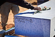 """18 MARCH 2010 - SURPRISE, AZ: Tom Lanphear (CQ) from Phoenix, places flowers and dirt in the shape of a cross on the caskets, including the casket of an unknown man, during burials in White Tanks Cemetery on Camelback Rd. in an unincorporated part of the county near Surprise. The county spent about $2.5 million to inter indigent people in what is Maricopa County's """"potters field.""""  About 3,000 people, children and adults, are buried in the dusty field west of Phoenix.       PHOTO BY JACK KURTZ"""