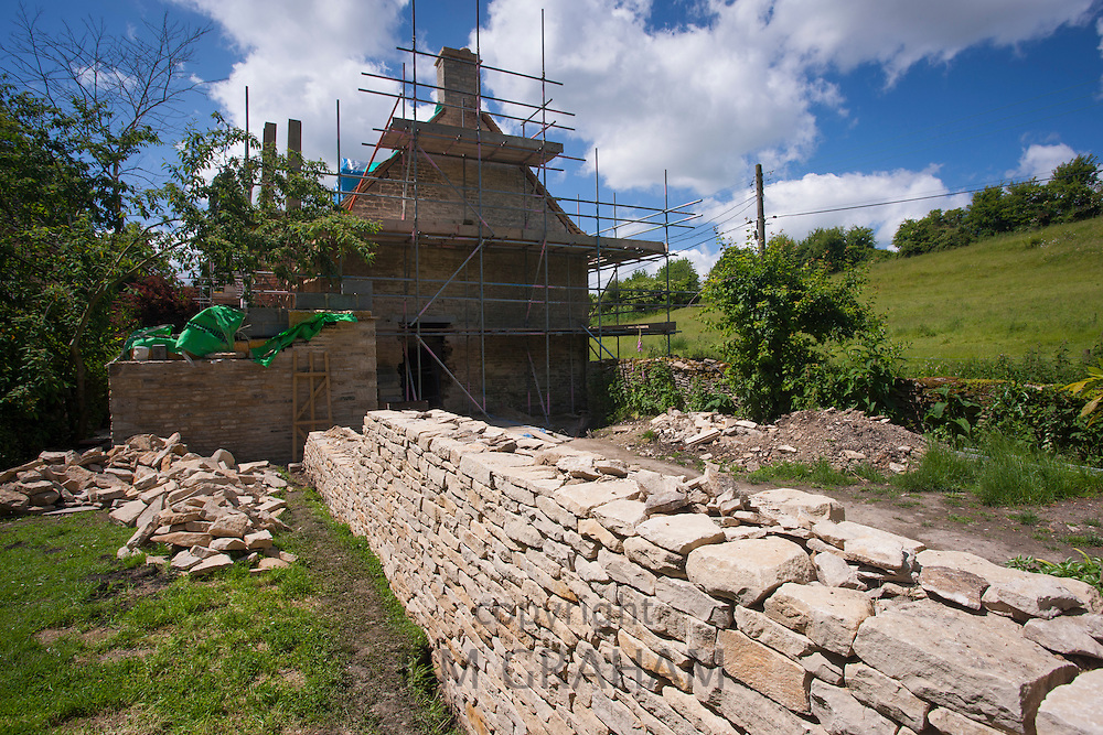 Renovation and new built dry stone wall constructed of new Cotswolds stone using traditional method at period property, UK