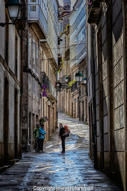 A gentleman wearing a backpack and carrying hiking poles arrives in Santiago de Compostela after walking the Camino.