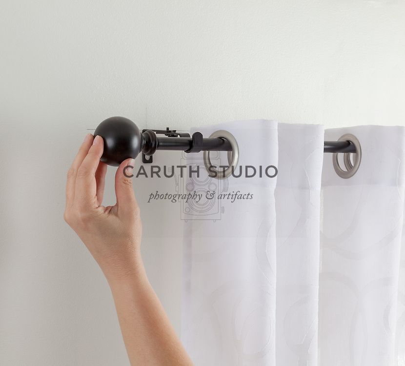 How to hang curtains: placing curtain rod on bracket and attaching finial