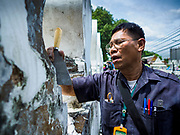 23 AUGUST 2017 - BANGKOK, THAILAND: A Bangkok city worker uses a scraper to remove old paint and dirt from the walls of Pom Mahakan. Bangkok city officials this week started cleaning up the area around cremation site for Bhumibol Adulyadej, the Late King of Thailand. Work started by cleaning Pom Mahakan, a historic fort about two kilometers northeast of the cremation site. They are going to scrub and paint the fort's historic exterior walls, which were built in the late 18th century. The King, who died on 13 October 2016, will be cremated on 26 October 2017.      PHOTO BY JACK KURTZ