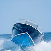 Small boat speeding over an ocean swell