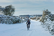 Cyclist in snowy lane cycling in country lane in The Cotswolds, UK