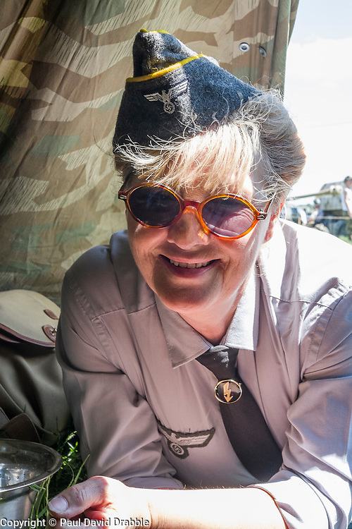 A female re-enactor portrays a Wehrmacht Heferin with the German Army in work uniform blouse shelters from the sun in the shade of a Zeltbahn. Wehrmacht Heferinnen were he German Armed Forces female Auxiliaries. At various periods o time during world war two they were sometimes classified as military personnel other times as uniformed civilians employed by the German Armed Forces (Wehrmacht)<br />