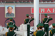 Tian'anmen Square (Place of Heavenly Peace). Flag lowering ceremony at sunset. Police and the portrait of Mao Zedong at Tian'anmen gate.