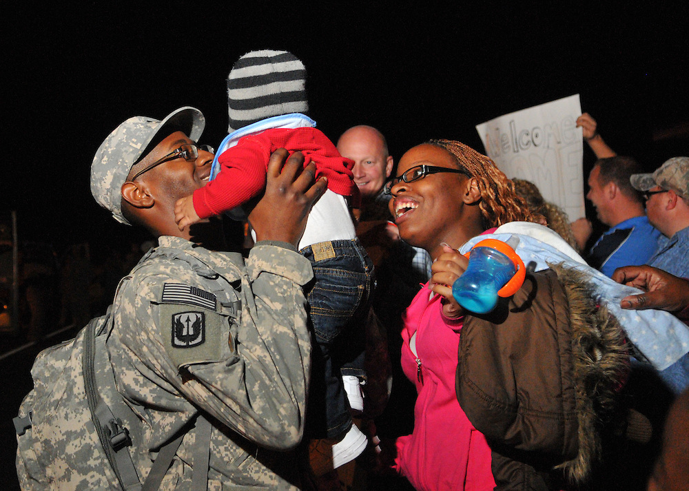 Specialist Mario Antonie Jackson holds his 6-month-old son TreMarion while his wife Shaneese looks on Tuesday night at Camp Shelby. Jackson was one of two bus loads of the 185th Aviation division of the Mississippi National Guard who returned home from Iraq to Camp Shelby. Bryant Hawkins/ Hattiesburg American