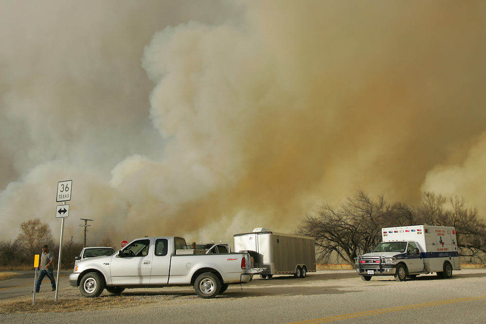 Photo by Alex Jones..Paramedics and Callahan county residents wait on Highway 36 on the West side of Cross Plains on the afternoon of Tuesday, December 27, 2005, as a massive grass fire sweeps through the area.