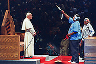 Pope John Paul II receives a Native American blessing during a meeting with various tribes in Phoenix, Arizona.  The 1987 Papal Tour to the United States covered eight cities.