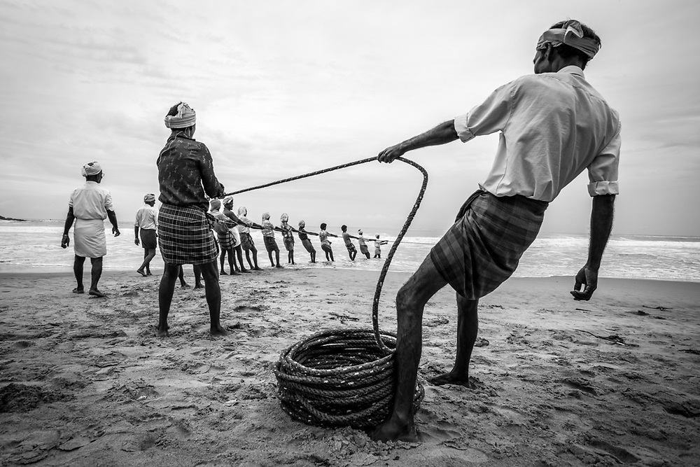 Kerala, India. A fishermen team from Kovalam is pulling toward the beach the fishing nets.<br />