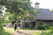 Family walking towards a barn at Meadow Mist Farm in Lexington Massachusetts in July of the summer of 2018.