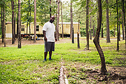 LOWNDES COUNTY, AL – JULY 10, 2017: Aaron Thigpen, 29, observes a site where raw sewage is dumped through a PVC pipe only a few yards away from a home. Thigpen, a community activist in nearby Fort Deposit, was part of a recent study conducted by Baylor University that exposed he prevalence of hookworm in Lowndes County residents.<br /> <br /> A recent study conducted by Baylor University suggests that nearly one 1 in 3 people in Lowndes County have hookworm, a parasite normally found in poor, developing countries. Below ground septic tanks are common in Lowndes, but due to the chalky clay soil throughout much of the Black Belt, septic tanks are prone to backing up into people's homes during heavy rains. With failing or absent municipal sewage systems in the county, many families choose to live with open, above ground sewer systems made from PVC pipe, which pump raw sewage into nearby streams or open land.