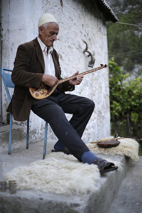 Martin Pisha, 82 years old, inhabitant of Theth, playing the traditional lahuta instrument.  Albania