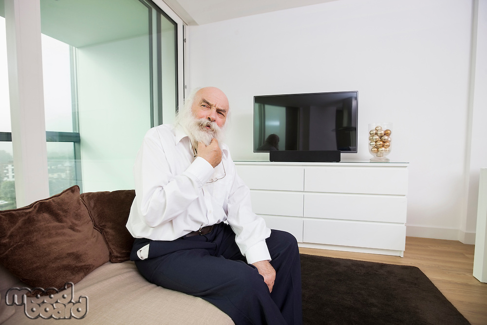 Thoughtful senior man sitting on sofa in living room
