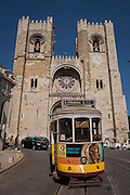The number 12 tram descends steep streets past the Se Cathedral in Lisbon, Portugal.