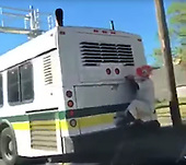 Clown hitches a ride on the back of a bus