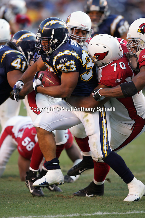 SAN DIEGO - DECEMBER 31:  Running back Michael Turner #33 of the San Diego Chargers runs the ball while being gang tackled by defensive tackle Kendrick Clancy #70 and the Arizona Cardinals at Qualcomm Stadium on December 31, 2006 in San Diego, California. The Chargers defeated the Cardinals 27-20 to secure the number one seed in the AFC playoffs. ©Paul Anthony Spinelli *** Local Caption *** Michael Turner;Kendrick Clancy