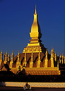 A motorcycle with two passengers passes That Luang monument in Vientiane, Laos during the late afternoon. The gold covered Buddhist stupa is a national monument of Laos and was built in the 3rd century.