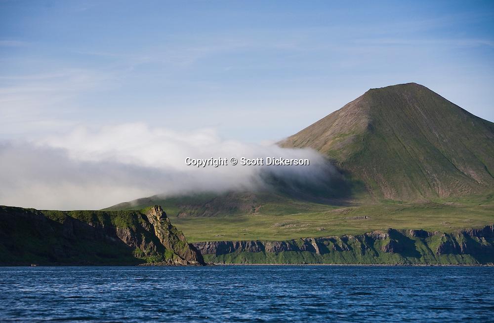 The ever changing weather of the Aleutian Islands seeps over a green mountain ridge near False Pass, Alaska.