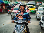 29 NOVEMBER 2015 - BANGKOK, THAILAND:   A man and his son on their motorcycle in the Amulet Market on Maharat Road in Bangkok. Hundreds of vendors used to sell amulets and Buddhist religious paraphernalia to people in the Amulet Market, a popular tourist attraction along Maharat Road north of the Grand Palace near Wat Maharat in Bangkok. Bangkok municipal officials announced that they are closing the market and forcing vendors to relocate to an area about one hour outside of Bangkok. The closing of the amulet market is the latest in a series of municipal efforts to close and evict street vendors and markets from areas that have potential for redevelopment. The street vendors were evicted from the area on Sunday, Nov. 29.      PHOTO BY JACK KURTZ