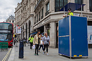"In the 24hrs that a further 38 died from Coronavirus, bringing the total to 41,736, a further easing of the UK's Covid pandemic lockdown restrictions took place with many high street shops today being allowed to re-open after three months of forced closure. Prime Minister Boris Johnson, wanting to stimulate the economy, has urged people to ""shop with confidence"" and long queues formed outside the main brands. But unlike on public transport, face coverings are not compulsory so shop floors and shopping practices have had to be adapted to ensure customers' social distances, amid fears of a second infection wave. A police officer is positioned on an especially-built raised scaffolding platform to watch the public at this important moment of economic progress, on Regent Street, on 15th June 2020, in London, England."