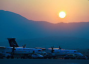 Greece, Athens Airport, Olympic Airlines Dash8 passanger planes on the ground at sunset