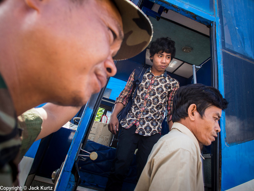 16 JUNE 2014 - POIPET, CAMBODIA: Cambodian migrants returning from Thailand get off a bus in Poipet, Cambodia. More than 150,000 Cambodian migrant workers and their families have left Thailand since June 12. The exodus started when rumors circulated in the Cambodian migrant community that the Thai junta was going to crack down on undocumented workers. About 40,000 Cambodians were expected to return to Cambodia today. The mass exodus has stressed resources on both sides of the Thai/Cambodian border. The Cambodian town of Poipet has been over run with returning migrants. On the Thai side, in Aranyaprathet, the bus and train station has been flooded with Cambodians taking all of their possessions back to Cambodia.  PHOTO BY JACK KURTZ