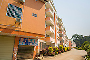13 MARCH 2013 - ALONG HIGHWAY 13, LAOS: A nearly empty Chinese hotel and condo development near the end of Highway 13 in the Boten Special Economic Zone. The SEZ is in Laos immediately south of the Lao Chinese border. It has turned into a Chinese enclave but many of the businesses struggle because their goods are too expensive for local Lao to purchase. Some of the hotels and casinos in the area have been forced to close by the Chinese government after reports of rigged games. The paving of Highway 13 from Vientiane to near the Chinese border has changed the way of life in rural Laos. Villagers near Luang Prabang used to have to take unreliable boats that took three hours round trip to get from the homes to the tourist center of Luang Prabang, now they take a 40 minute round trip bus ride. North of Luang Prabang, paving the highway has been an opportunity for China to use Laos as a transshipping point. Chinese merchandise now goes through Laos to Thailand where it's put on Thai trains and taken to the deep water port east of Bangkok. The Chinese have also expanded their economic empire into Laos. Chinese hotels and businesses are common in northern Laos and in some cities, like Oudomxay, are now up to 40% percent. As the roads are paved, more people move away from their traditional homes in the mountains of Laos and crowd the side of the road living off tourists' and truck drivers.    PHOTO BY JACK KURTZ