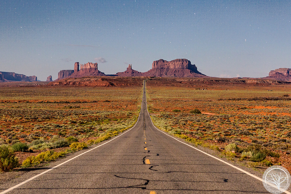 A night image of Forrest Gump Hill taken under the full moon, with Monument Valley and a sky full of stars in the background. Utah US highway 163, mile marker 13.