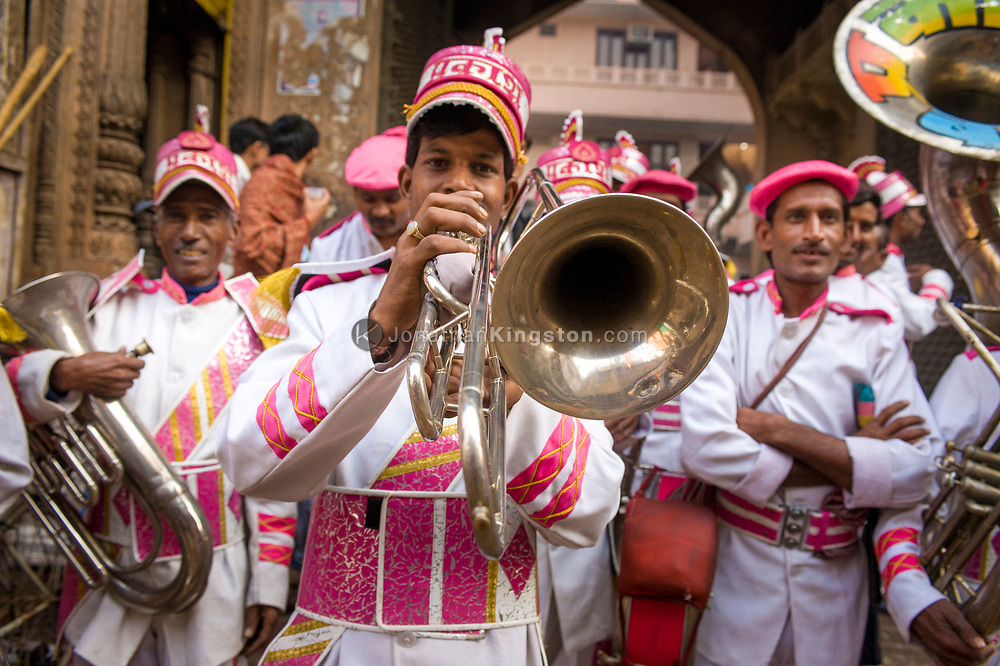 Marching band members prepare to perform for a wedding, Mathrua, India.