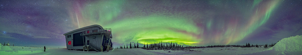 A 270&deg; panorama from southwest to northeast taking in the full sweep of the auroral arcs this night, January 29, 2017 at the Churchill Northern Studies Centre, on the shore of Hudson Bay in Churchill, Manitoba. Sirius and Orion are at far left. The Pleiades is over CNSC. Arcturus is at far right. A lone aurora observer stands at left. Someone is also on the second floor deck. A bit of an isolated arc is at right to the east. <br /> <br /> This is a stitch of 11 segments, each 10 seconds at f/2 with the Sigma 20mm Art lens and Nikon D750 at ISO 3200. Stitched with Adobe Camera Raw.
