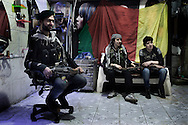 "SYRIA, ALEPPO : Kurdish fighters from the ""Popular Protection Units"" (YPG) sit in their headquarter (former hair salon) in the majority-Kurdish Sheikh Maqsud district of the northern Syrian city of Aleppo, on April 16, 2013. ALESSIO ROMENZI"
