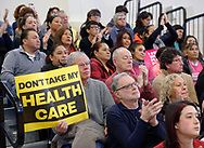 "Westbury, New York, USA. January 15, 2017.  A man holding a yellow and black sign saying ""Dont Take My Health Care"" sits on crowded bleachers with other protestors at the ""Our First Stand"" Rally against Republicans repealing the Affordable Care Act, ACA, taking millions of people off health insurance, making massive cuts to Medicaid, and defunding Planned Parenthood. ."