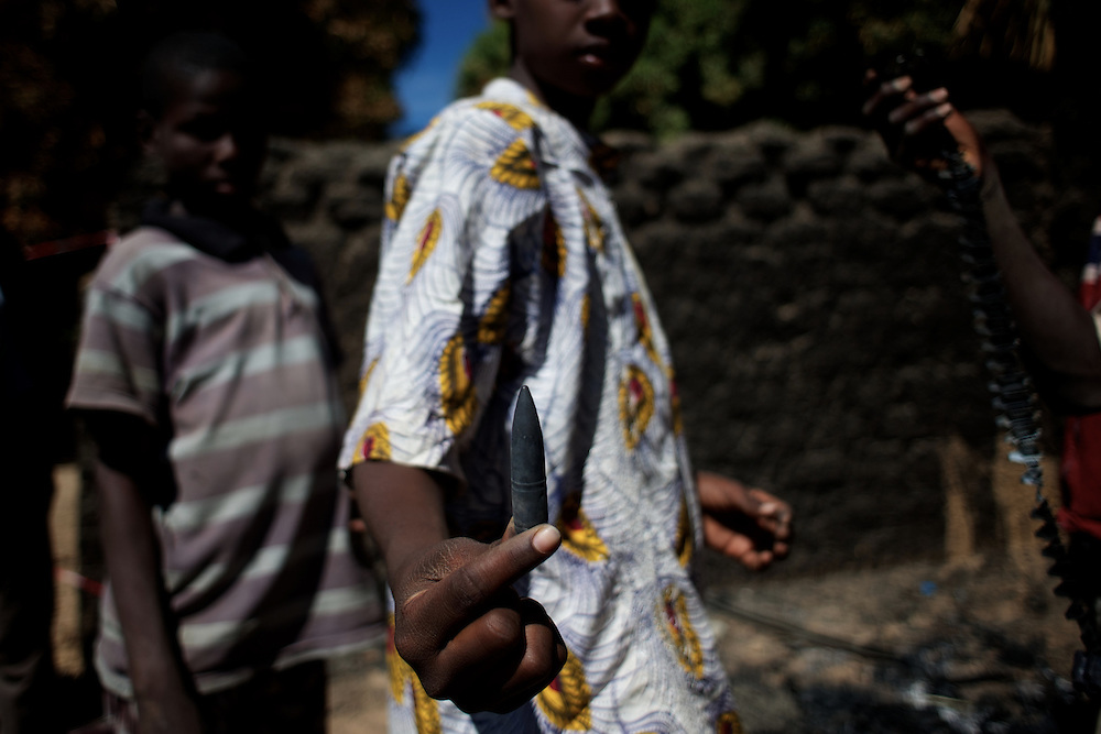 January 21, 2013 - Diabaly, Mali: Local children scavenge destroyed islamic militants' armoured vehicles in central Diabaly, a day after Mali government troops regain control of the city. Diabaly was under islamist militants control since the 14th of January.<br /> <br /> Several insurgent groups have been fighting a campaign against the Malian government for independence or greater autonomy for northern Mali, an area known as Azawad. The National Movement for the Liberation of Azawad (MNLA), an organisation fighting to make Azawad an independent homeland for the Tuareg people, had taken control of the region by April 2012.<br /> <br /> The Malian government pledge to the French army to help the national troops to stop the rebellion advance towards the capital Bamako. The french troops started aerial attacks on rebel positions in the centre of the country and deployed several hundred special forces men to counter attack the advance on the ground. (Paulo Nunes dos Santos)