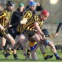 """Ballyea's Gearoid O'Connell shoulders Alan Mulready Sixmilebridge as he goes to ground during the Minor """"A"""" Hurling Final. - Photograph by Flann Howard"""