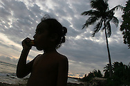 A young boy at dusk on the beach on the island of Kiribati in the South Pacific. The islands, and their way of life, is endangered by rising sea water levels which are eroding the fragile atoll, home to approximately 92,000 people.