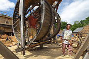 Man walking in the squirrel cage of the lifting gear with double drum, an early form of crane, on the building site in the courtyard at the Chateau de Guedelon, a castle built since 1997 using only medieval materials and processes, photographed in 2017, in Treigny, Yonne, Burgundy, France. The Guedelon project was begun in 1997 by Michel Guyot, owner of the nearby Chateau de Saint-Fargeau, with architect Jacques Moulin. It is an educational and scientific project with the aim of understanding medieval building techniques and the chateau should be completed in the 2020s. Picture by Manuel Cohen