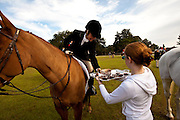 An attendant serves glasses of port to a mounted Fox Hunter before the start of the hunt in front of the plantation house at Middleton Place plantation in Charleston, SC.