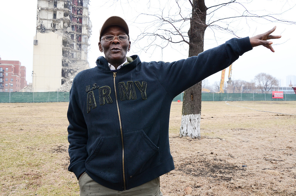 Norman Campbell, a former pharmacy technician and Cabrini Green resident, gestures in the direction of where he lived in the Cabrini public housing complex as the last of the doomed project buildings is demolished behind him. April, 2011.