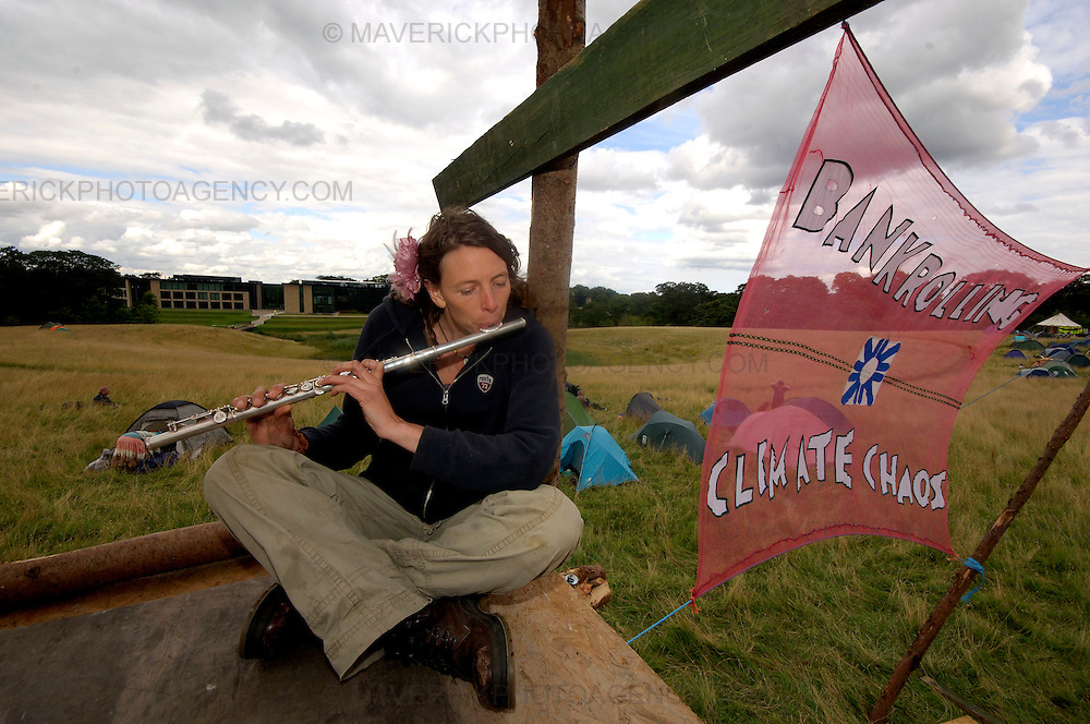 EDINBURGH, UK - 19th August 2010: Climate change protesters have set up camp close to the Royal Bank of Scotland headquarters in Edinburgh...The Camp for Climate Action is protesting about RBS's role in financing oil industry developments...Picture shows Kate Pasteur playing her flute to entertain campers whilst they set up camp with RBS HQ at Gogarburn in the background...(Photograph: Richard Scott/MAVERICK)