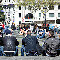 Jovenes descansan en la plaza de Cataluña. Barcelona, España. Young relaxing on the Plaza Catalunya. Barcelona, ​​Spain.