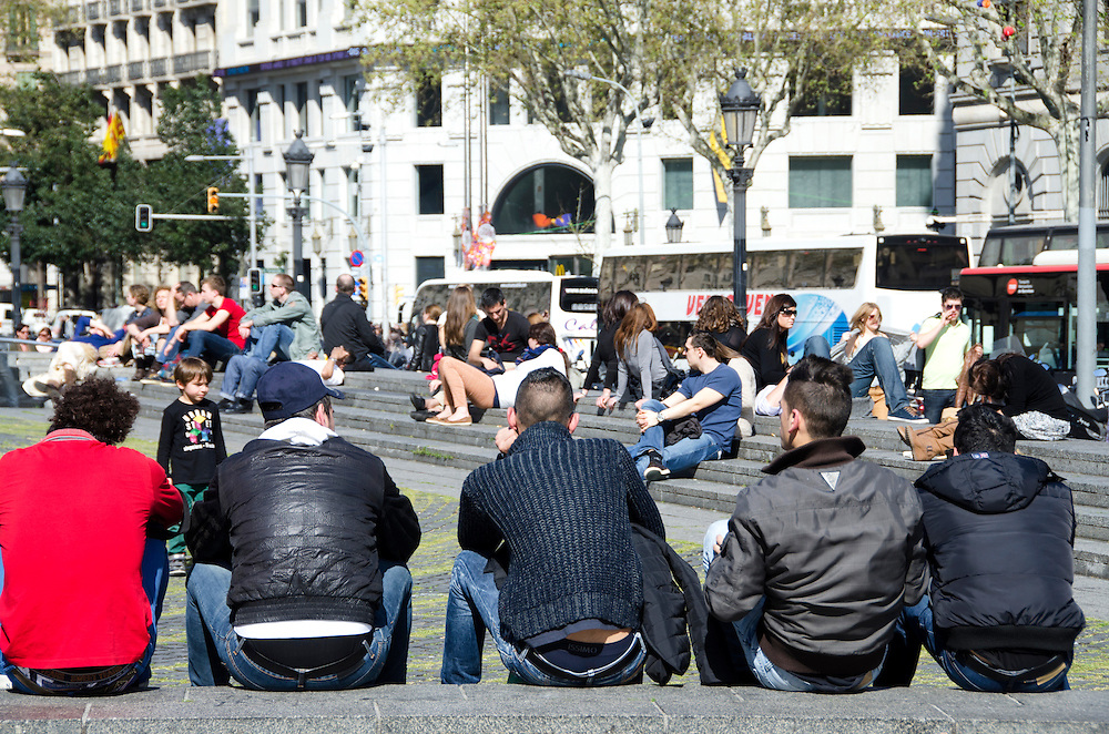 Jovenes descansan en la plaza de Cataluña. Barcelona, España. Young relaxing on the Plaza Catalunya. Barcelona, Spain.