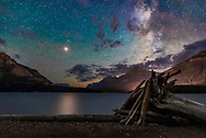 Bright yellow Mars approaching a close opposition in July 2018 shines over the waters of Middle Waterton Lake in Waterton Lakes National Park in southwest Alberta on the Alberta-Montana border. Mars is so bright it produces a glitter path on the water. <br /> <br /> The Milky Way is at right. This was from Driftwood Beach, windy as always this night.<br /> <br /> The sky is tinted green with bands of airglow, though there was a dim aurora to the north this night as well, quite unexpected. <br /> <br /> Waterton Lakes is a World Heritage Site and a Dark Sky Preserve. <br /> <br /> This is a stack of ten exposures for the ground to smooth noise (and blur the wind-rippled water) at f/3.2, and a single exposure for the sky at f/2.2, all 30 seconds with the Sigma 24mm Art lens and Nikon D750 at ISO 6400. Taken July 11/12, 2018 at the end of a 6-hour session training the Dark Sky Guides staff. It was a superb night, with everything to see in the sky.