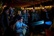 Visitors stand around a television displaying election results during an election party for George P. Bush at Joe T. Garcias in Fort Worth, Texas on March 4, 2014. (Cooper Neill / for The Texas Tribune)